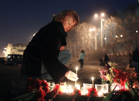 A woman lights a candle in Kiev in memory of protesters who died